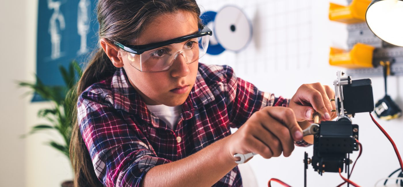 Girl in a robotics laboratory adjusts the robot arm model,